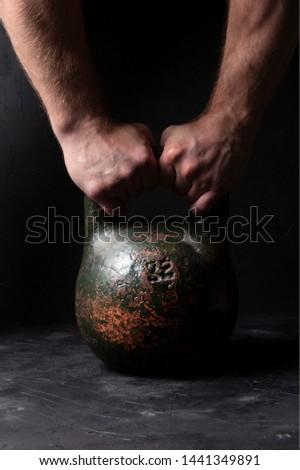 Man holds old heavy sports weight 32 kg on dark background