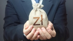 Man holds out a polish zloty money bag. Budget management, collect taxes. Insurance payout. Financial crisis support, benefits, subsidies. Bank issuance of credit and loans borrowings to business.