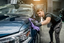 Man holds the microfiber in hand and polishes the car. Car detailing