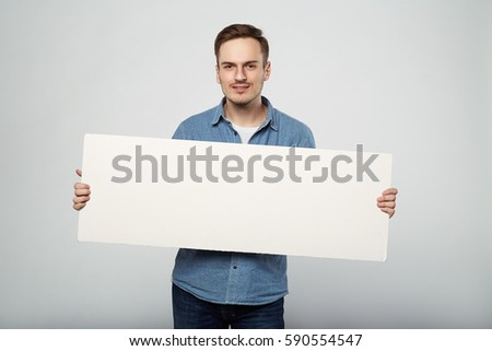 man holds the white sign in a studio white background #590554547