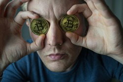 Man holds two bitcoins. Male with bitcoins  in eyes. Bitcoin is a cryptocurrency invented in 2008 by an unknown person or group of people using the name Satoshi Nakamoto. The currency began use in 200
