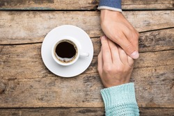 Man holds woman's hand with cup of coffee top view image on wooden backdrop. Friendship coffee background