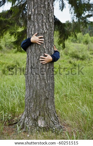 Man hugging a big tree bole in the forest