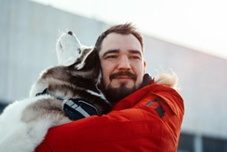 Man hugging Siberian Husky dog on a walk in modern park on sunny winter day. Pure love and friendship