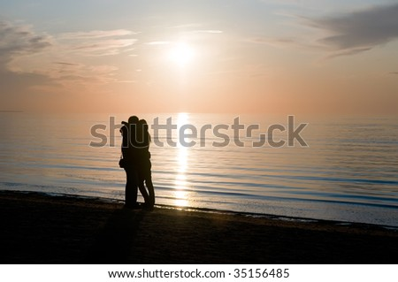 Man hugs a girl ashore sea on a background sunset