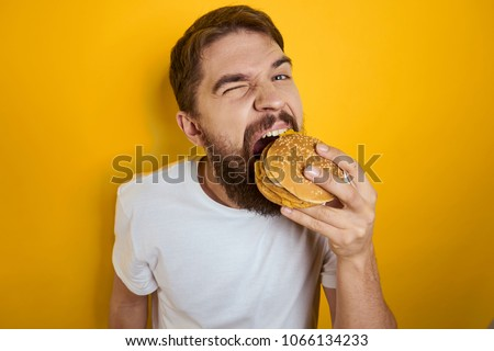 man hungry eating a hamburger                               #1066134233