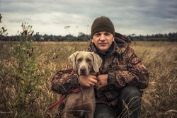 Man hunter with hunting dog Weimaraner friend portrait in rural field during hunting season