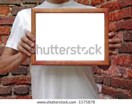 Man i white t-shirt shows your text or picture in wooden frame