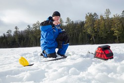 Man ice fishing on a northern Minnesota lake on a sunny winter morning