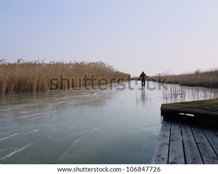Man ice-skating on lake Neusiedl. The photo was taken in Burgenland, Austria.