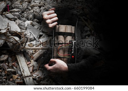 Man in a black jacket strapped with explosives and detonator holds in his hand #660199084