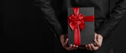 Man in a black shirt holds a gift with a red ribbon behind his back. Black gift box in hands. Surprise.