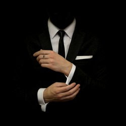 Man in a black suit and white shirt and black tie on a black background. Without a face. The businessman in the dark. Studio shot