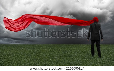 Man in a black suit with a red cloth is in the green field, loneliness, dreams, sleep, red fabric, storm clouds