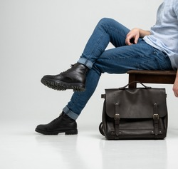 Man in a blue jeans and black boots sits on a chair with a brown men's shoulder leather bag for a documents and laptop on a white floor. Mens leather satchel, messenger bags, handmade briefcase.