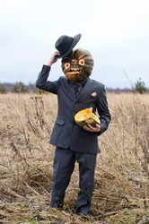 man in a business suit and with a Halloween pumpkin on his head stands in the autumn yellowed field lifting his hat, perhaps he is greeting