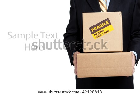 Man in a business suit holding moving boxes with a fragile sticker on it on a white background