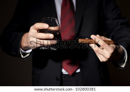 man in a business suit holds a cigar and a glass with whiskey