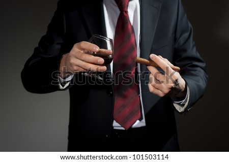 man in a business suit holds a cigar and a glass with whisky