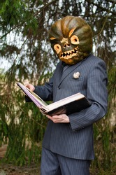 man in a business suit with a Halloween pumpkin on his head reads an old book