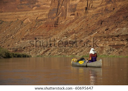 Man in a canoe on a desert river in the Utah canyon country