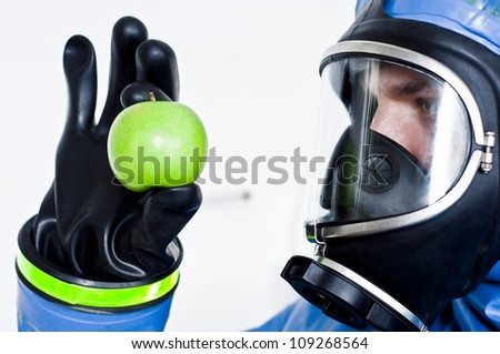 Man in a chemical suit and gas mask holding contaminated apple - isolated white background