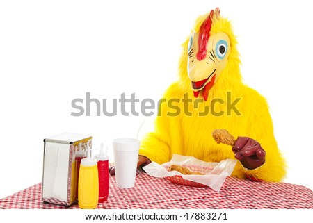 Man in a chicken suit sitting down to eat a fried chicken dinner.  Isolated on white.