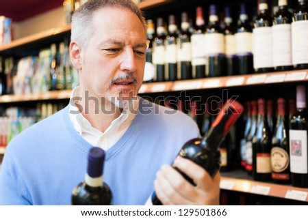 Man in a comparing two wines bottles