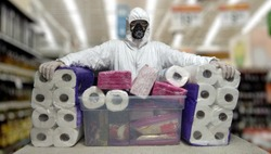 Man in a disposable face mask gloves and white suit while in panic shopping in a supermaket due to corona virus crisis