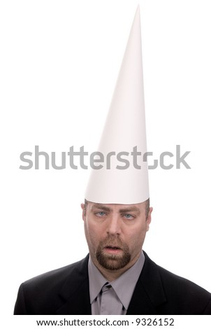 Man in a dunce cap with eyes crossed over a white background