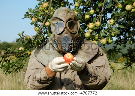 Man in a gas mask holding contaminated apple