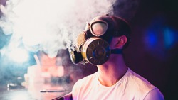 man in a gas mask Smoking a hookah and blowing smoke. Soft focus and small grain