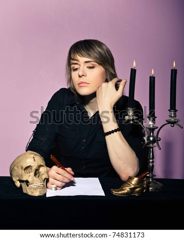 man in a gothic setting writes a letter