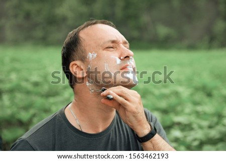 man in a gray t-shirt shaves outdoors Stock fotó ©