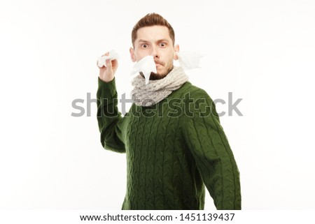 Man in a green sweater has runny nose and battles it with napkin.