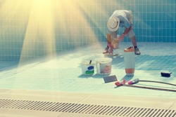 Man in a hat put the tiles on the bottom of the poolin the sunlight . Toned