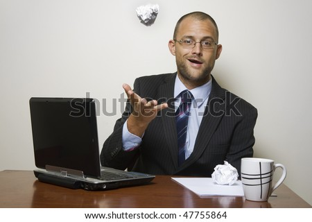 Man in a home office throwing a ball of paper in the air.
