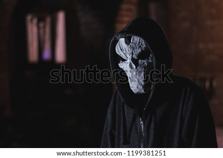Stock Photo man in a hood and skull mask on a black background