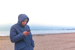 Man in a jacket on the beach by the sea with a mobile phone. Winter at sea.