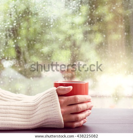 man in a light jumper, holds in hands red mug on a background of a wet window after the rain / hot drink and watch the rain