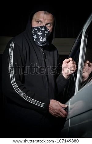 Man in a mask trying to steal car