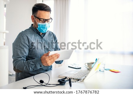 Man in a medical mask at the office. The man stayed at home and works remotely. The guy uses a Tablet PC and a laptop for work, and medicine mask and antiseptic for self protective