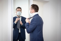 man in a medical mask corrects his tie in front of the mirror during the covid-19 pandemic. Concept of returning to work after reopening the economy.