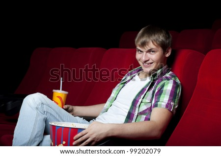 man in a movie theater, watching a movie and drink a drink