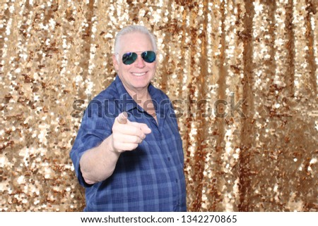 Man in a Photo Booth. A man smiles and poses in a Photo Booth with Gold Sequin Curtains. Photo Booths are fun for all guest.