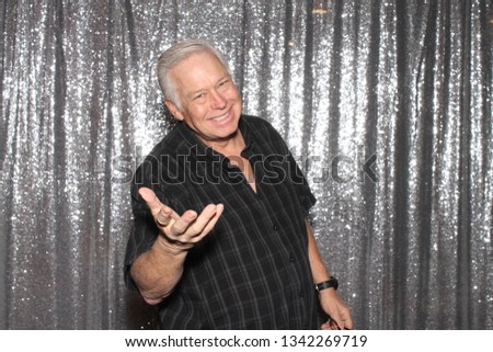 Man in a Photo Booth. A man smiles and poses in a Photo Booth with silver sequin curtains. Photo Booths are fun for all guest.