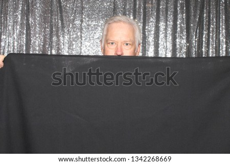 Man in a Photo Booth. A man smiles and poses with a black table cloth in a Photo Booth. Photo Booths are fun for all guest.
