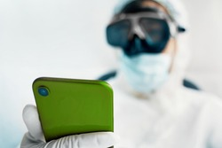 Man in a protective suit mask and gloves uses a green smartphone for communication with family. Epidemic pandemic new rapidly spreading coronavirus 2019-ncov, medicine flu virus concept.