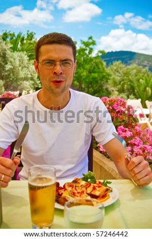 man in a restaurant holding fork and knife in his hands, he is going to have a dinner