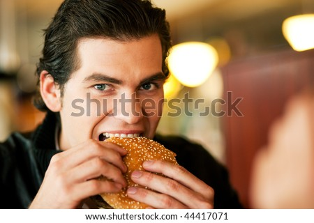 Man in a restaurant or diner eating a hamburger, he is hungry and having a good bite, shot with available light, very selective focus #44417071
